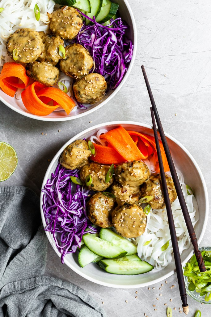 2 bowls of Asian-inspired chickpeas balls, rice noodles and fresh veggies with coconut curry sauce