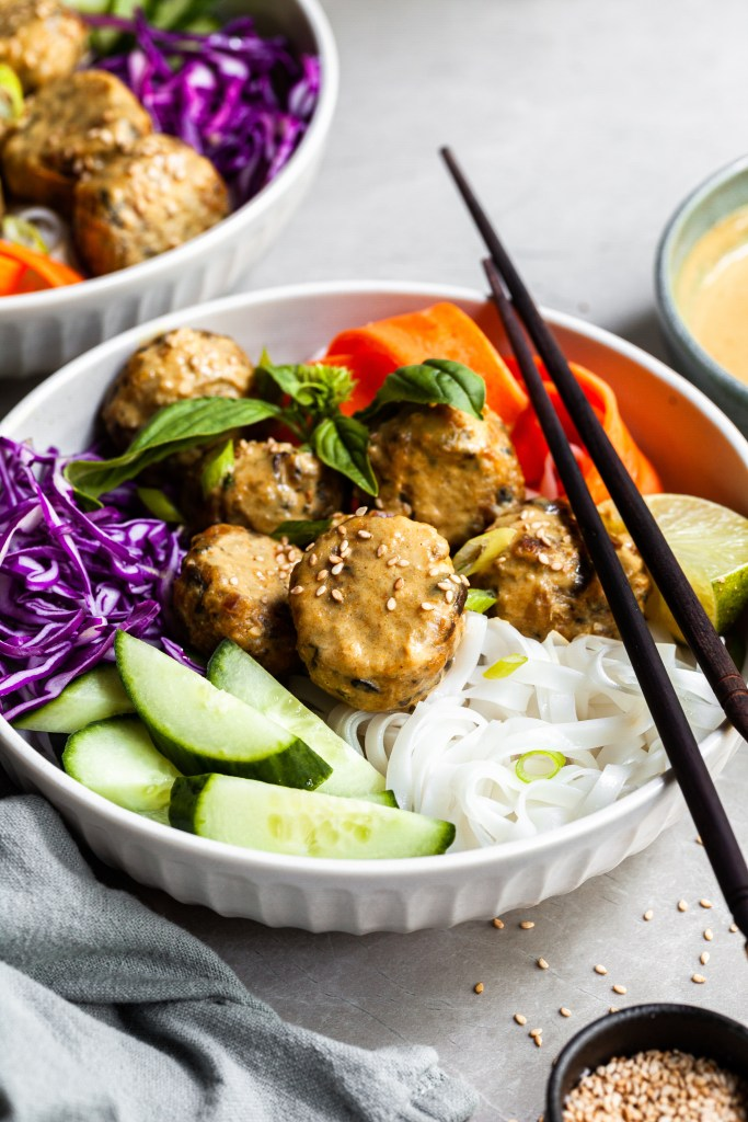 Thai inspired bowl of rice noodles with fresh veggies, chcikpea meatballs and coconut curry sauce