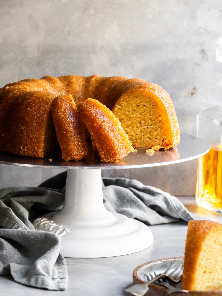 Sliced rum bundt cake on cake stand and a slice on a plate in the foreground