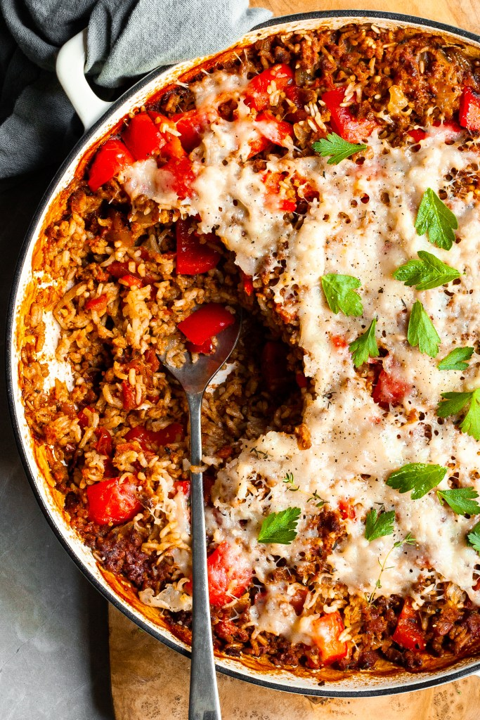 Close up of a white skillet with a serving of pepper and rice casserole scooped out