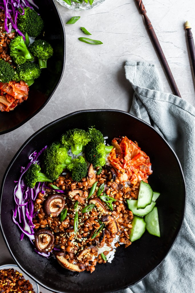 Flatlay of 2 black bowls filled with rice topped with lentils and mushrooms, broccoli, cucumbers and kimchi