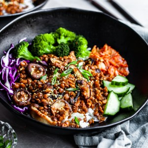 Angled view of a black bowl filled with rice topped with lentils, shiitakes, broccoli and kimchi