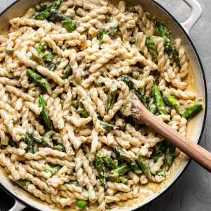 Flat lay of creamy lemon pasta with asparagus and peas in a white enamel skillet