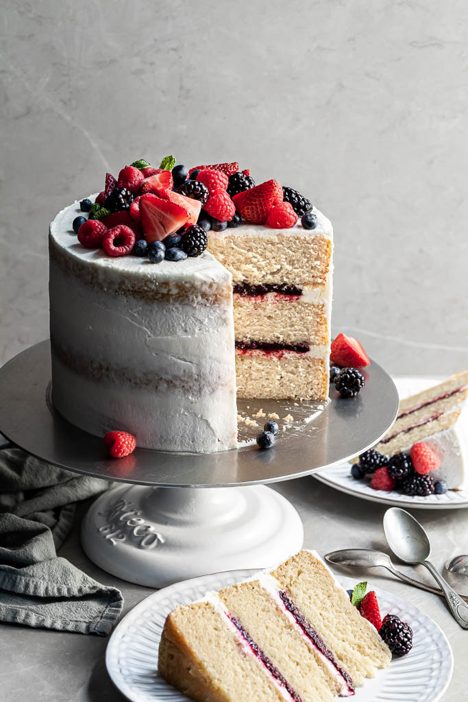 Vanilla berry layer cake with 2 slices cut resting on white plates, garnished with fresh berries.