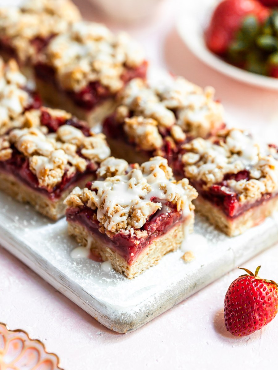 2 rows of strawberry oat bars on a narrow white cutting board
