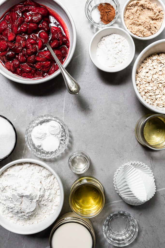 The ingredients for roasted strawberry muffins measured out in bowls on a marble counter