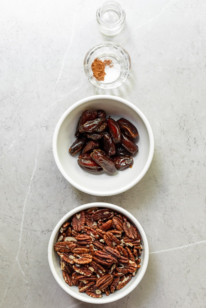 4 bowls on a marble counter with the ingredients for the no-bake crust - pecans, dates, cinnamon/salt, and vanilla extract