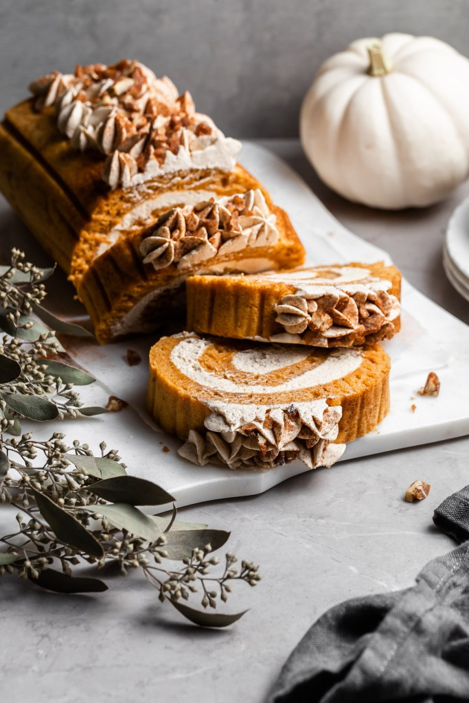 A pumpkin dessert roll resting on a white platter with three slices to be served and white plates at the side