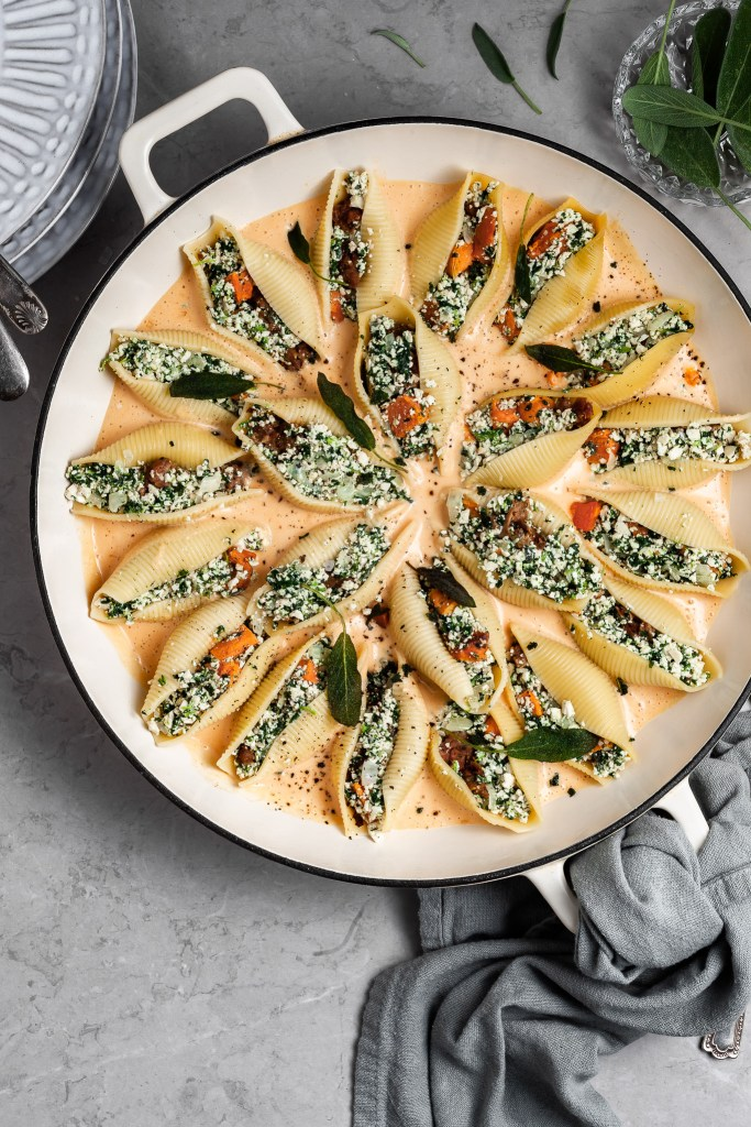 Jumbo pasta shells filled with vegan ricotta mixture are resting in a creamy sauce in a large white skillet before baking