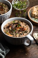 A white mug filled with creamy mushroom and rice soup with seared mushrooms garnishing the top.