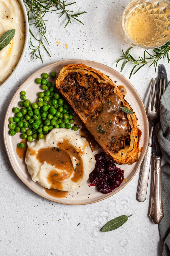 A slice of vegan Wellington on a plate with mashed potatoes, green peas, cranberry sauce and gravy.