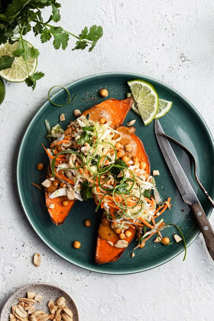 View looking down on a green plate filled with a sweet potato cut in half, topped with cripsy chickpeas, peanut sauce and coleslaw.