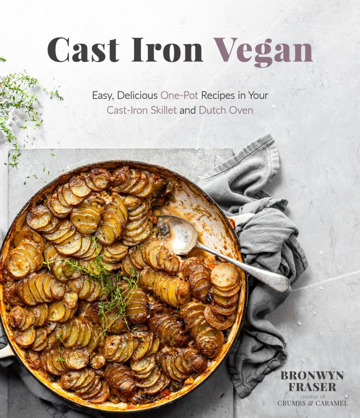 The front cover of the cookbook, Cast Iron Vegan, featuring a cottage pie in a white enamel skillet.