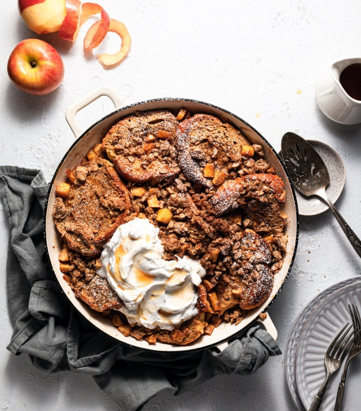 A white cast iron skillet filled with vegan overnight apple cinnamon French toast, garnished with whipper cream and maple syrup.