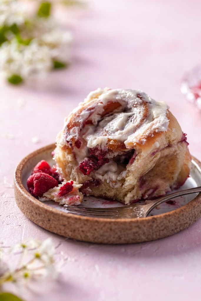 A single raspberry sweet bun with a bite missing sits on an artisan ceramic plate. White blossoms are bokahed in the background.
