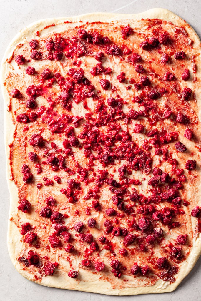 Sweet dough rolled out with vegan butter, raspberry preserves and frozen raspberries spread out on the top.
