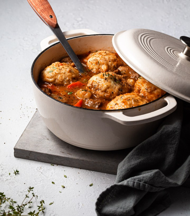A white enamel cast iron Dutch oven filled with a vegan beefy stew topped with dumplings.