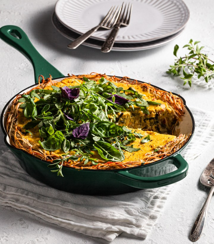 A green cast iron skillet filled with Mediterranean quiche with hashbrown crust, topped with spring greens and herbs.