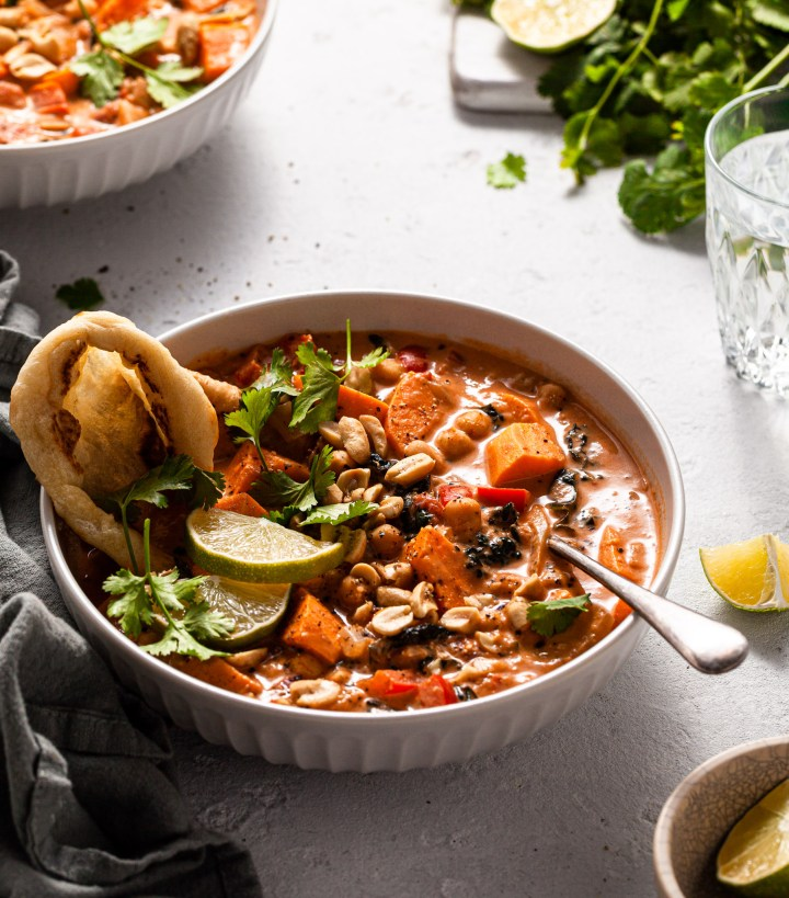 A white bowl cast in soft light filled with vegan sweet potato, chickpea and peanut soup.