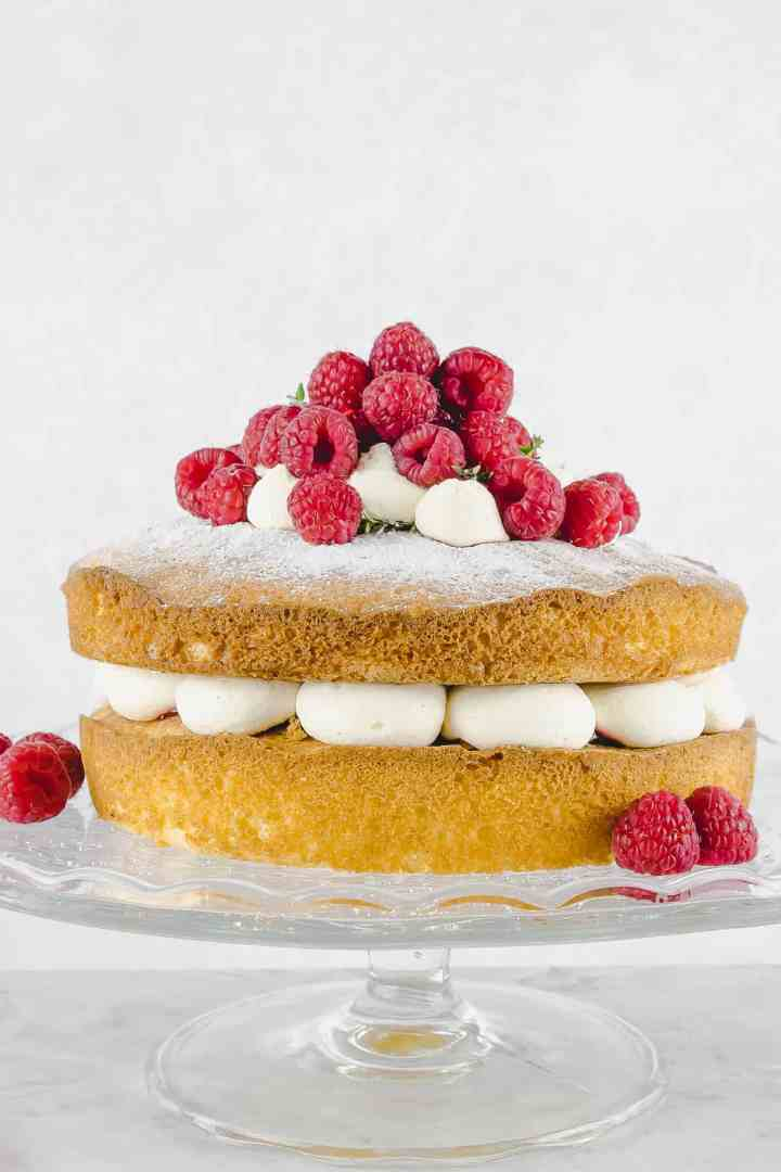 Raspberry Victoria sponge cake decorated with fresh raspberries on a cake stand