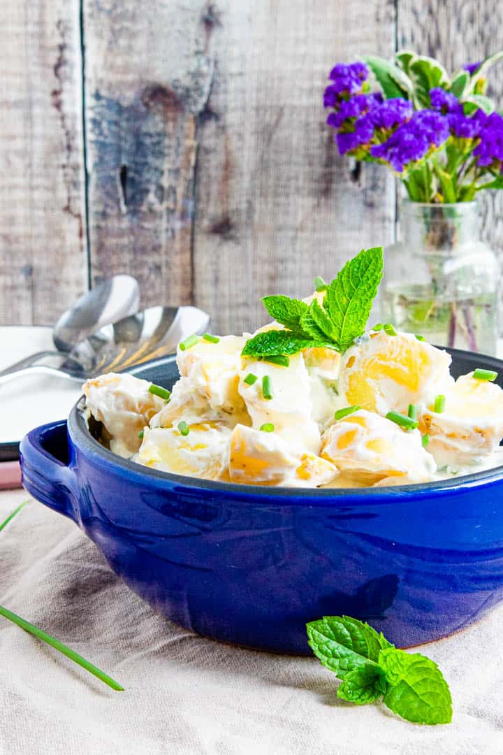 Blue bowl filled with easy low fat potato salad topped with chopped chives and a spring of mint