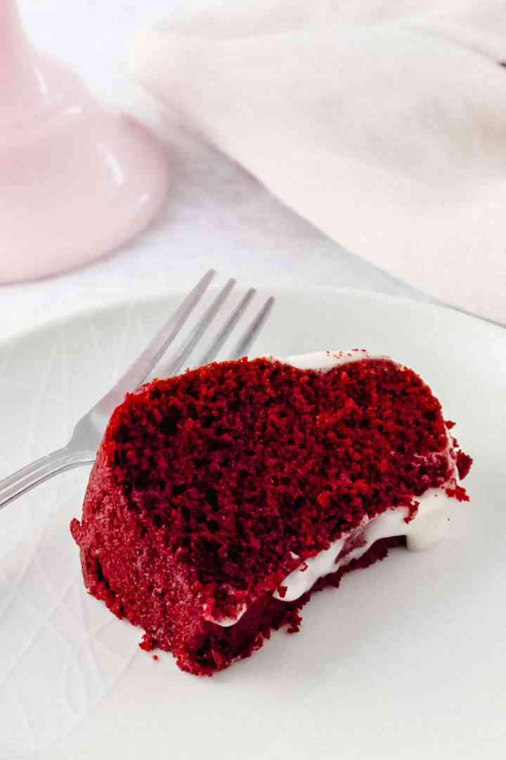 Slice of red coloured cake on a plate with a fork