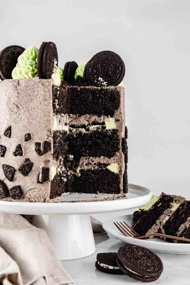Mint Oreo cake on a white cake stand with a slice cut out