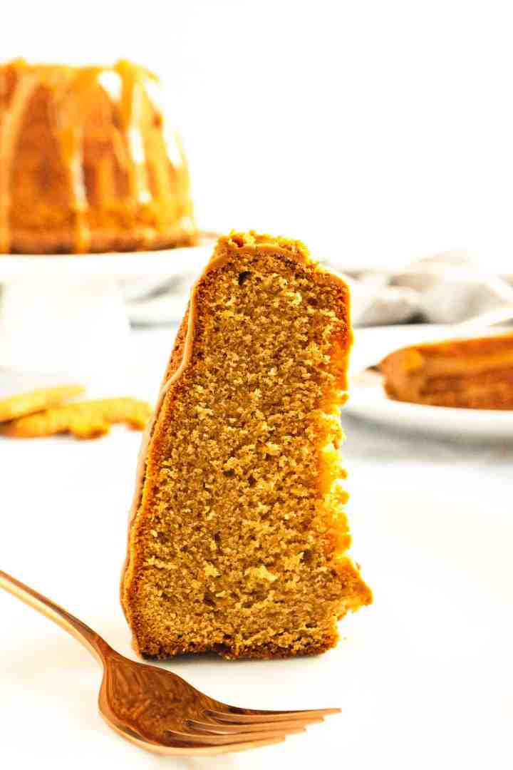 Slice of golden caramel cake on a white plate with a fork