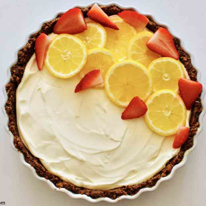 overhead shot of a no-bake lemon cheesecake decorated with slices of lemon and strawberries with a chocolate hobnob crust