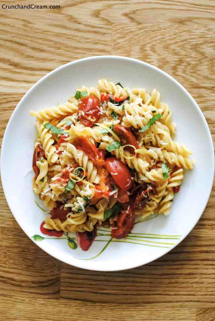 overhead image of a plate of fusilli pasta in a pile mixed with cooked tomatoes and diced chilli peppers, lemon zest and fresh herbs