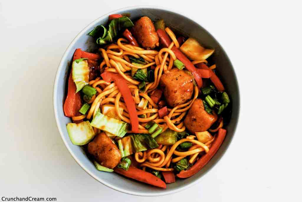 overhead of a deep bowl full of fresh egg noodles, red bell pepper, pak choi and spring onions with crispy diced halloumi pieces in a spicy sweet chilli sauce