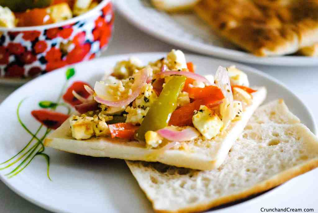 an open sandwich with pepper, tomato and onion roasted feta salad spread on it