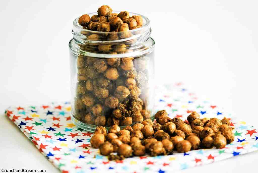 a jar of indian chickpeas on a patterned napkin scattered with more chickpeas