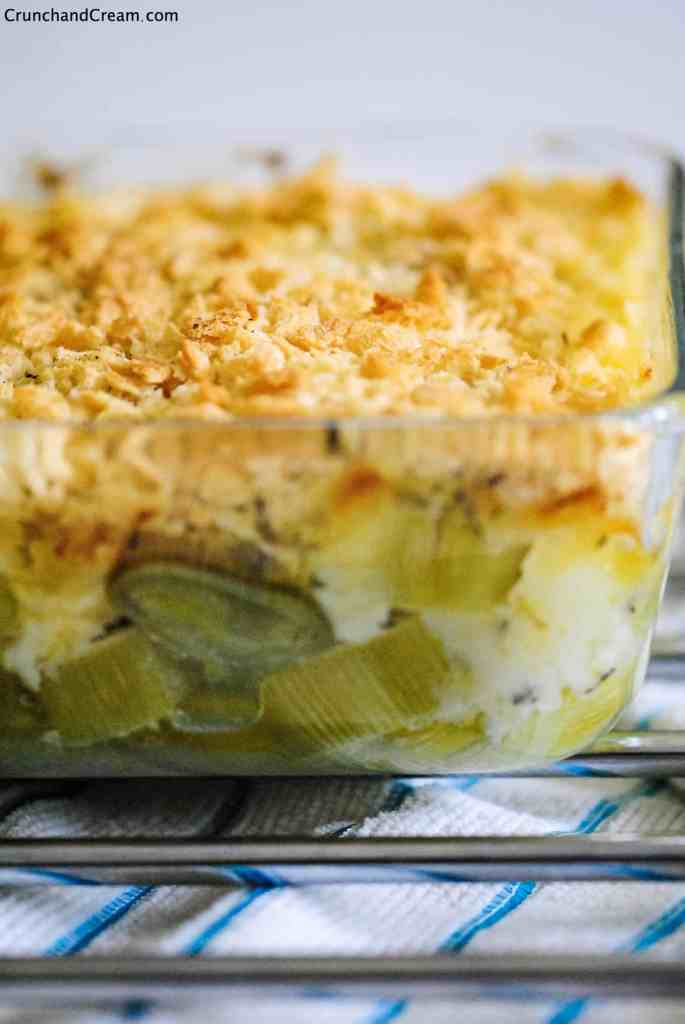 a clear dish of creamy leeks topped with breadcrumbs on a metal rack and kitchen towel