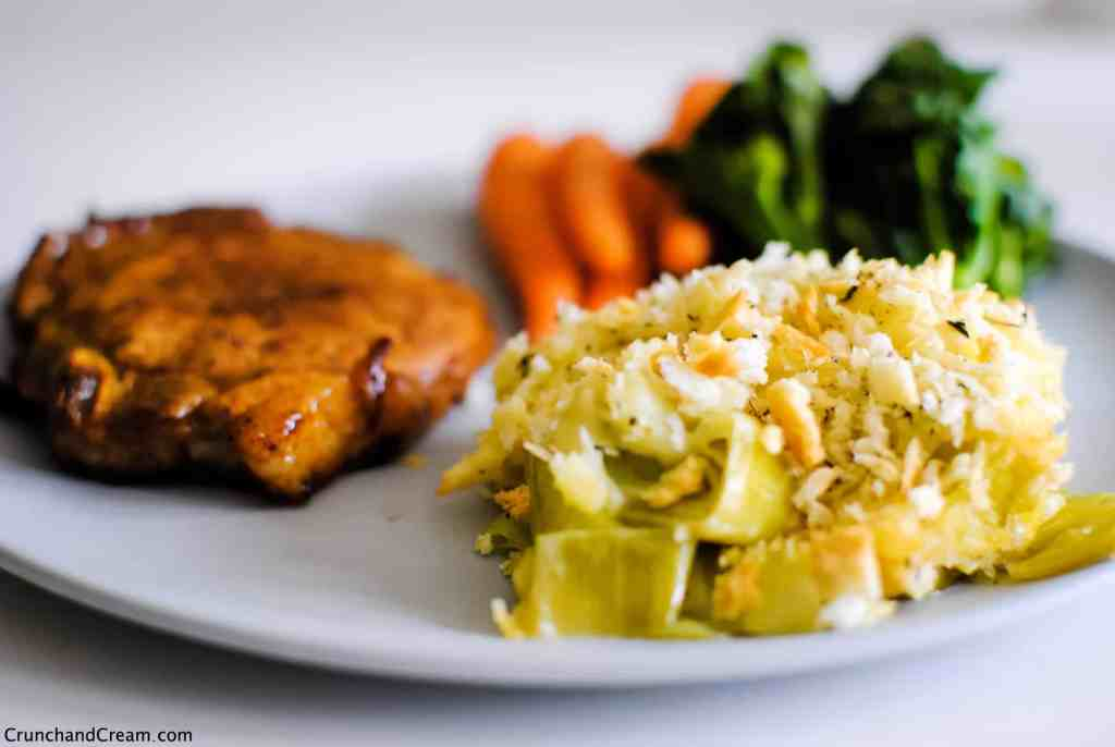 plate of cheesy, creamy leeks with golden breadcrumbs. Pork chop and steamed vegetables on the side.