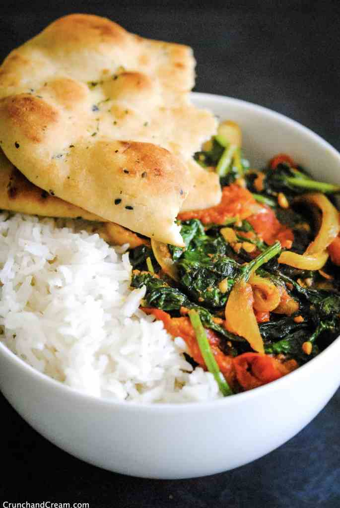 a bowl of vegan masala curry with spinach, onions and tomatoes, served in a bowl with basmati rice and torn naan bread