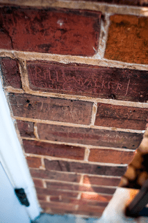 During it's time as a YMCA, children would sit on the ledge of this one time window, now door, and carve their names in the brick. Billy Walker is among the most prolific children to do so, carving his name all over the building.