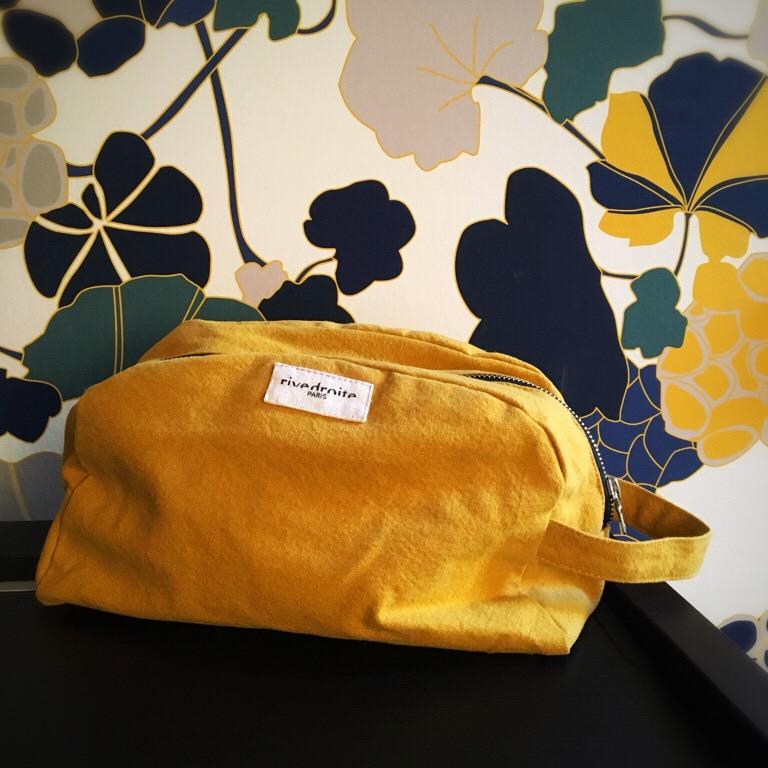 une trousse jaune posée devant un papier peint à grosses fleures jaunes et bleues.