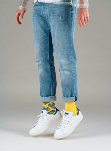 chaussettes dépareillés jaunes et à motifs portées dans des baskets blanches.