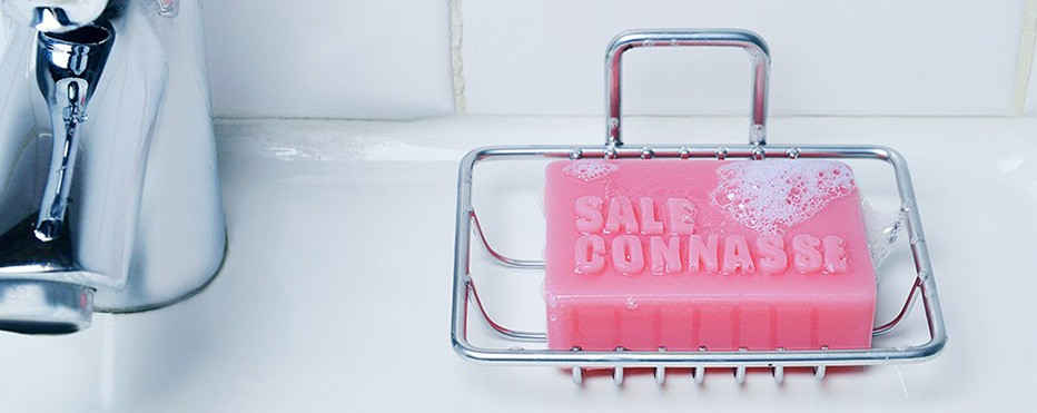 savon rose avec inscrit sale connasse en relief dans un porte savon métallique.