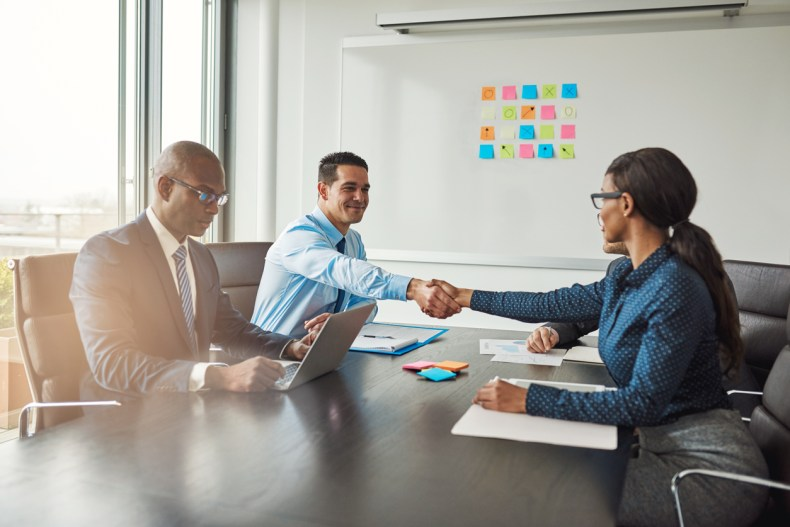 Two business colleagues shaking hands across the table in congratulations during a multiracial business meeting at a conference table in the office