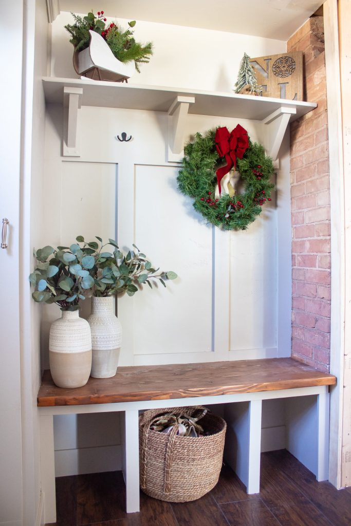 Finished entryway decorated for Christmas, showing one side with red brick