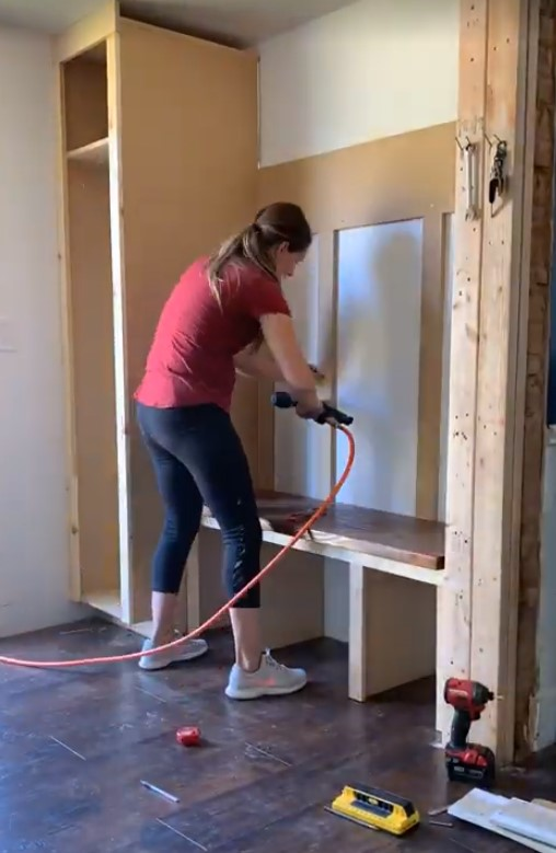Me adding board and batten to the back of my mudroom build