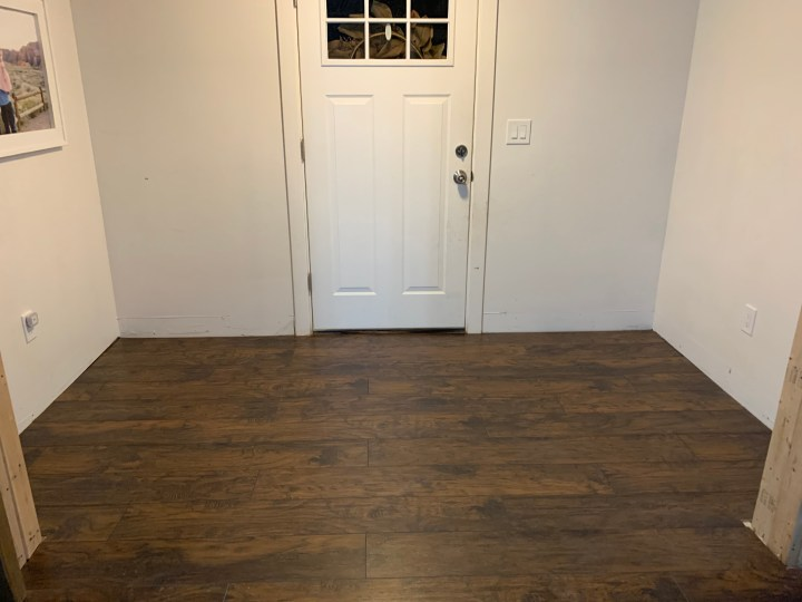 Entryway with blank white walls, front door and wood floor