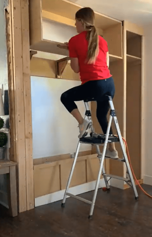 Me placing the upper cabinet carcass onto the top of the corbels on the wall