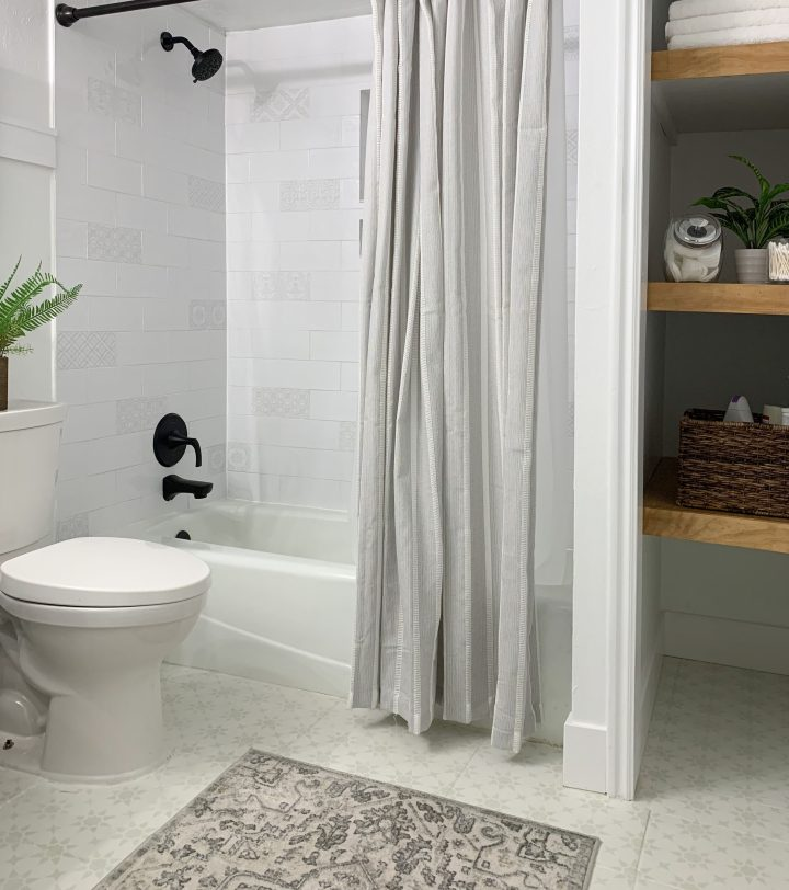 Finished shower with shower curtain and decor and white tile