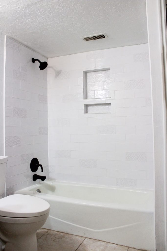 Finished shower with black faucet and white tile
