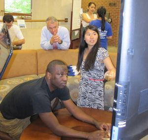 Olivier Mahame '14 (l) and Cathy Wang '15 (r) demonstrate the Collegium project to Chief Technology Officer David Saake.