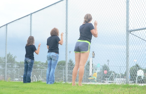CSC students glance through the fence at the closed Chadron Municipal Swimming Pool as discussion on a new pool project goes through Chadron City Council. — Photo Illustration by Teri Robinson