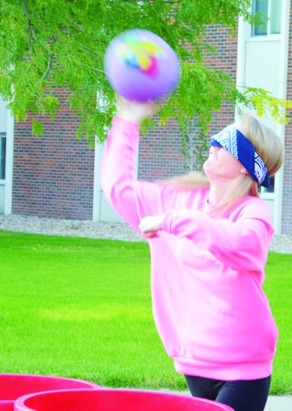Marci Luton, 19, sophomore of Grand Island, throws a kickball Monday for blind water pong. —Photo by Teri Robinson
